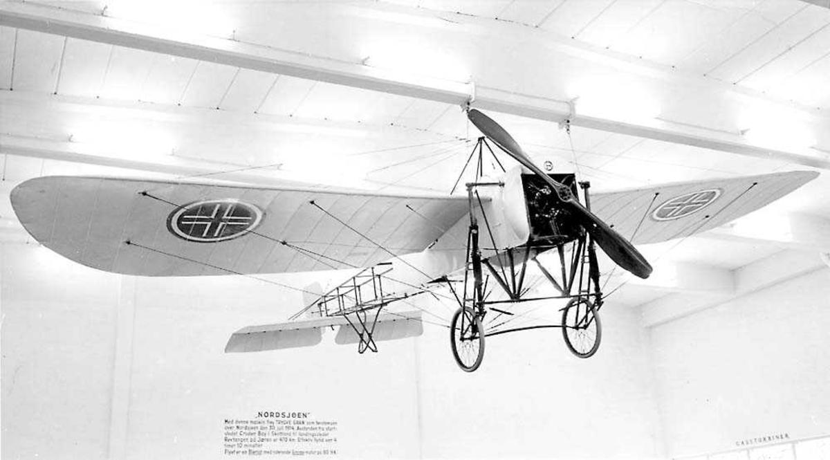 """Ett fly som henger i taket inne i en bygning, Bleriot XI """"Nordsjøen""""."""