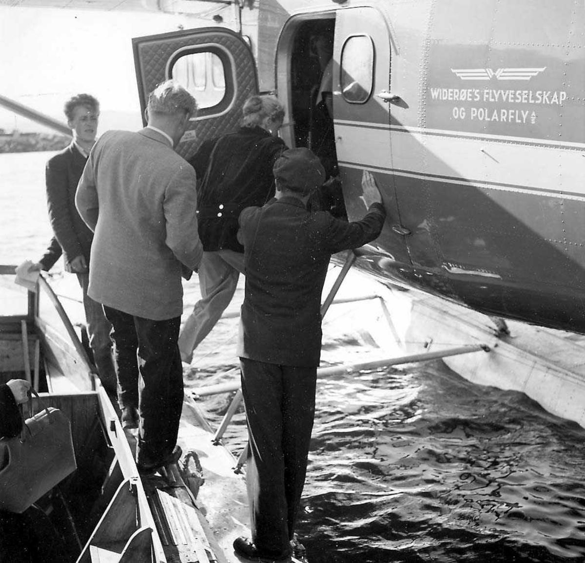 Flere passasjerer som klatrer ombord fra en båt til et sjøfly, DHC-3 Otter fra Widerøes Flyveselskap og Polarfly A/S.