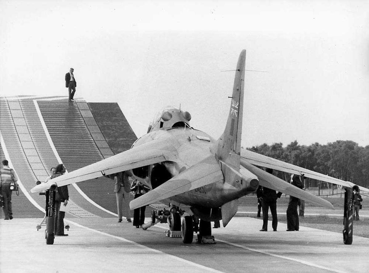Ett fly på bakken som står foran en rampe til take-off, Harrier. Flere personer rundt flyet.