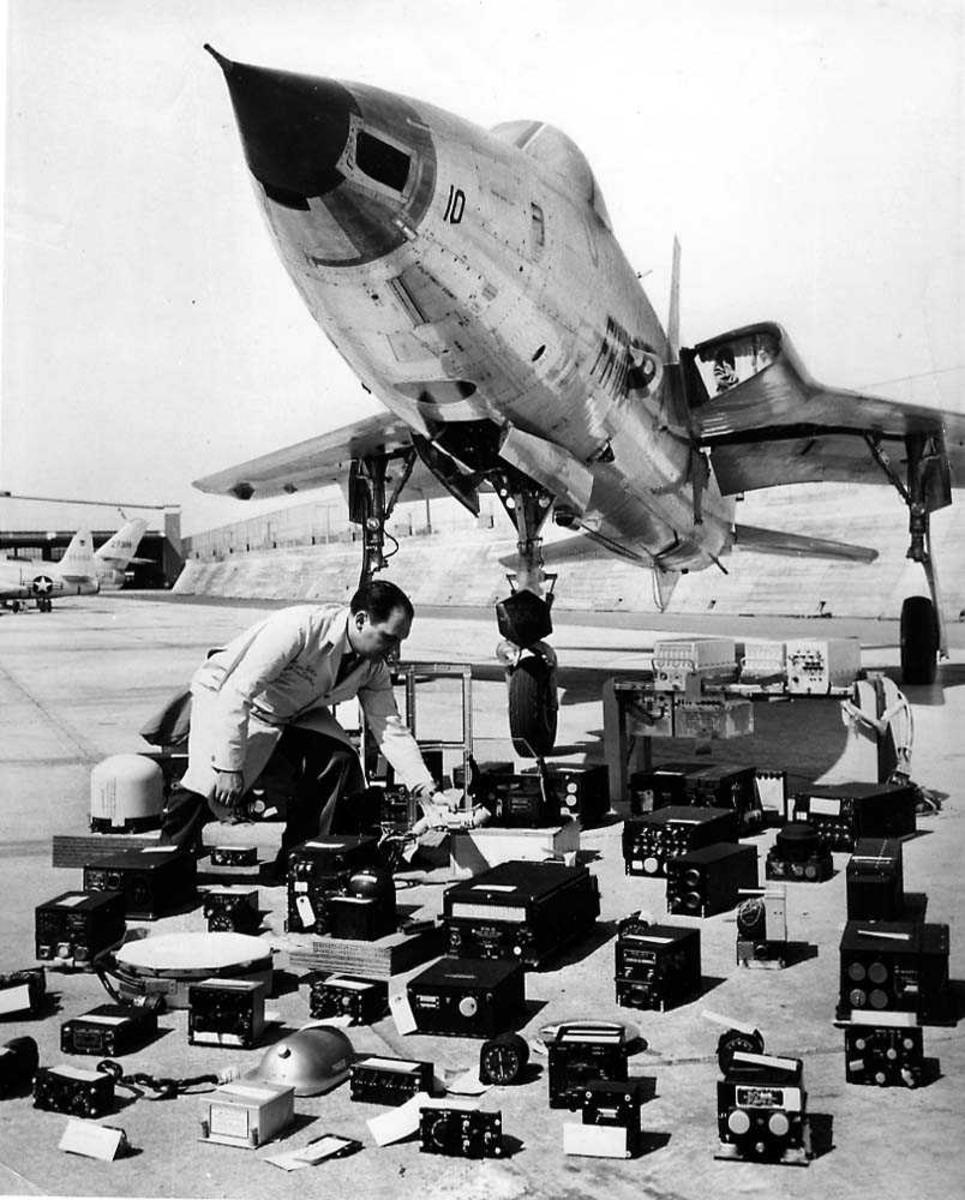 Ett fly på bakken med flere elektroniske instrumenter liggende foran flyet. Republic F-105D Thunderchief. En person ved instrumentene.