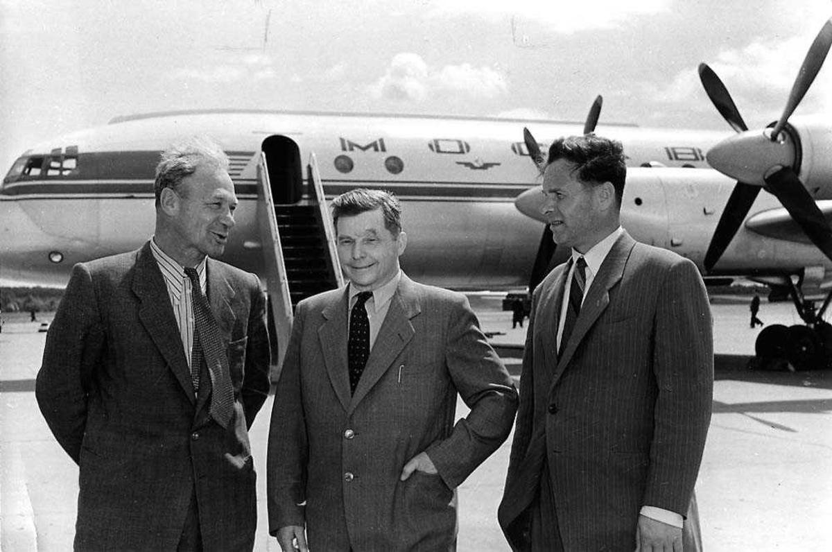 Portrett. Tre personer som står foran ett fly, Ilyushin Il-18 Coot.