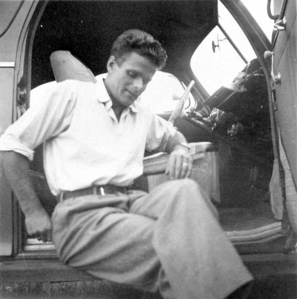 Portrett. En person, mann som sitter i døråpningen til en bil.