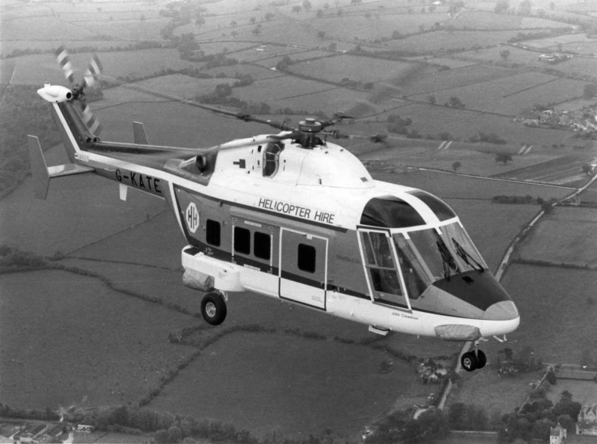 Ett helikopter i luften over dyrket mark. Westland 30-100 tilhørende Helicopter Hire Ltd, merket G-KATE