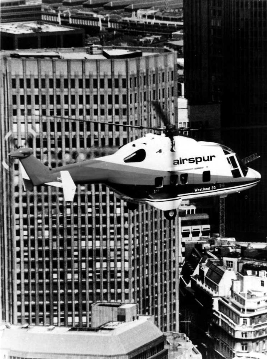 Ett helikopter i luften, over bykjerne. Westland 30 tilhørende Airspur Inc. Skyskrapere