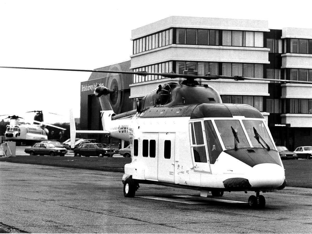 To helikopter på bakken, ett Westland 30 i forgrunnen merket G-BIWY. Ett Boeing CH-47 Chinook i bakgrunn. Kontorbygg og British airways helicopters hangar t.h. i bildet.