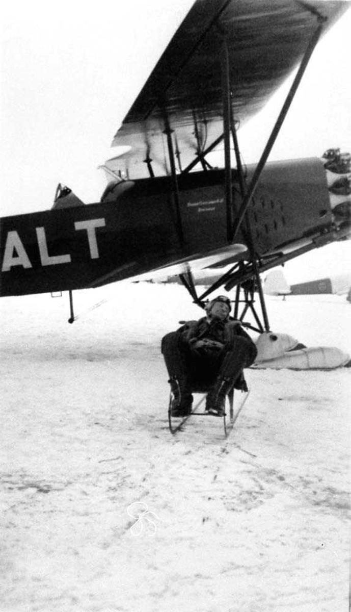 Ett fly på isen SE-ALT. En person ligger på en kjelke ved flyet. Snø på bakken.