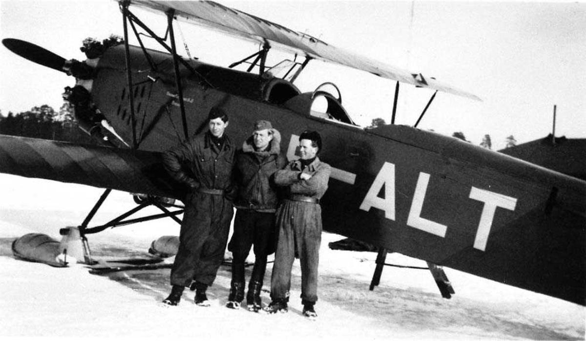 Ett fly på isen, SE-ALT. Tre personer står ved flyet. Snø på bakken.