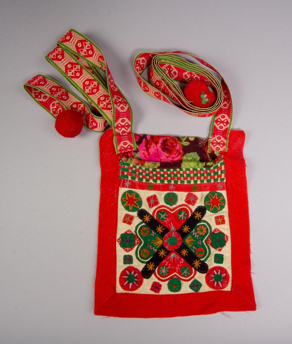 """Kjolsäck till dräkt för kvinna från Rättviks socken, Dalarna. Modell med avskuret framstycke. Framstycke av beige bomullstyg, satinvävt, med applikation av kläde i rött, grönt och svart, delvis fastsydda med maskinsöm. Centralt placerad hjärtblomma, omgiven av rundlar och stjärnor. Broderi utfört med bomullsgarn i många färger: kedjesöm, sticksöm och flätsöm. Ovanför applikationen fastsydd en remsa rött kläde, ovan den en """"grind"""" flätad av smala remsor rött och grönt kläde samt vitt fårskinn, ovan den en kantning av tryckt yllemuslin. En bred remsa rött kläde med utstickande kant inlagd i sido- och bottensöm, sydda hörn. Överstycke av yllemuslin med tryckt mönster. Framstycket fodrat med vitt bomullstyg, lakansväv. Bakstycke av bomullstyg, randigt i vitt och två blå toner. Band i två delar, fastsydda i överstycket och avslutade med bollar av ullgarn, handvävda, plockat mönster i rött ullgarn på vit botten. Bandet är  avslutat i yttre ändarna med en boll av rött ullgarn."""