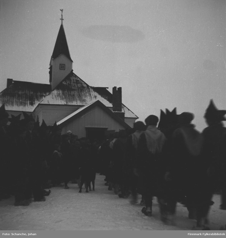 Kirkesøndag med bryllup i Karasjok kirke påsken -48.   Brudeparet, Berit Kristiane Samuelsdatter Balto og Kåre Karlsen Rudsether,  med slekt og andre gjester marsjerer to og to mot kirka.    På dette bildet er de i ferd med å gå inn i kirka. Folk står ved døråpningen og ser på følget.  Bildet er nesten identisk med førrige: FBib.95066-124, men på dette bildet står det mye mer folk ved døren, de fleste i samedrakt.
