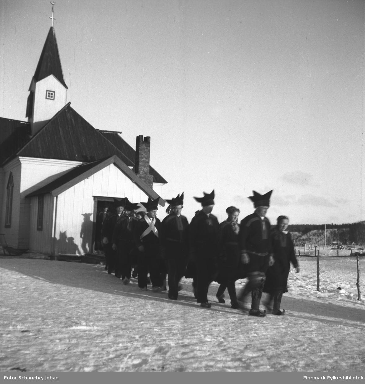 Kirkesøndag med bryllup i Karasjok kirke påsken -48.   Berit Kristiane Samuelsdatter Balto og Kåre Karlsen Rudsether gifter seg. Paret med slekt og andre gjester marsjerer ut av kirken på rekka i to og to. Brudeparet er den fjærde paret i rekka. Fremst går foreldrene til de nygifte.  Kirken til venstre.