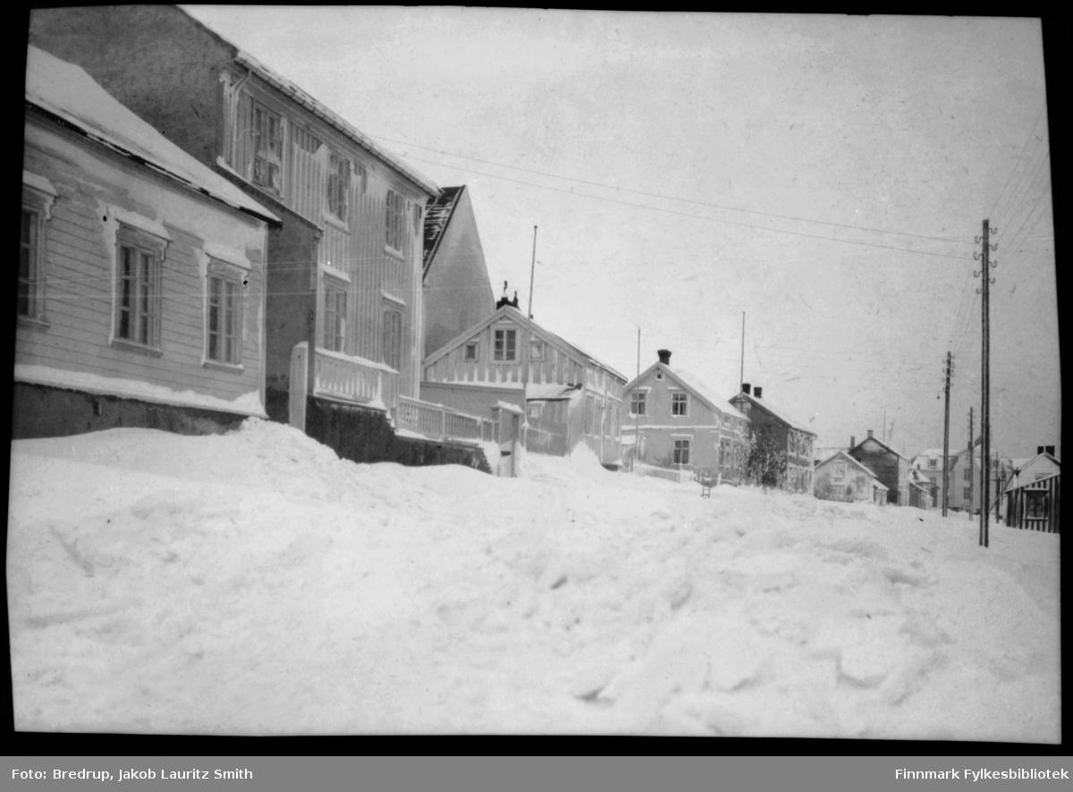 Inspektør Hansens gate i Vadsø.  Det har vært snøstorm, og husene er dekket med snø.  Midt i bildet en forlatt spark, den står forlatt omtrent der Kirkebakken krysser Inspektør Hansensgate