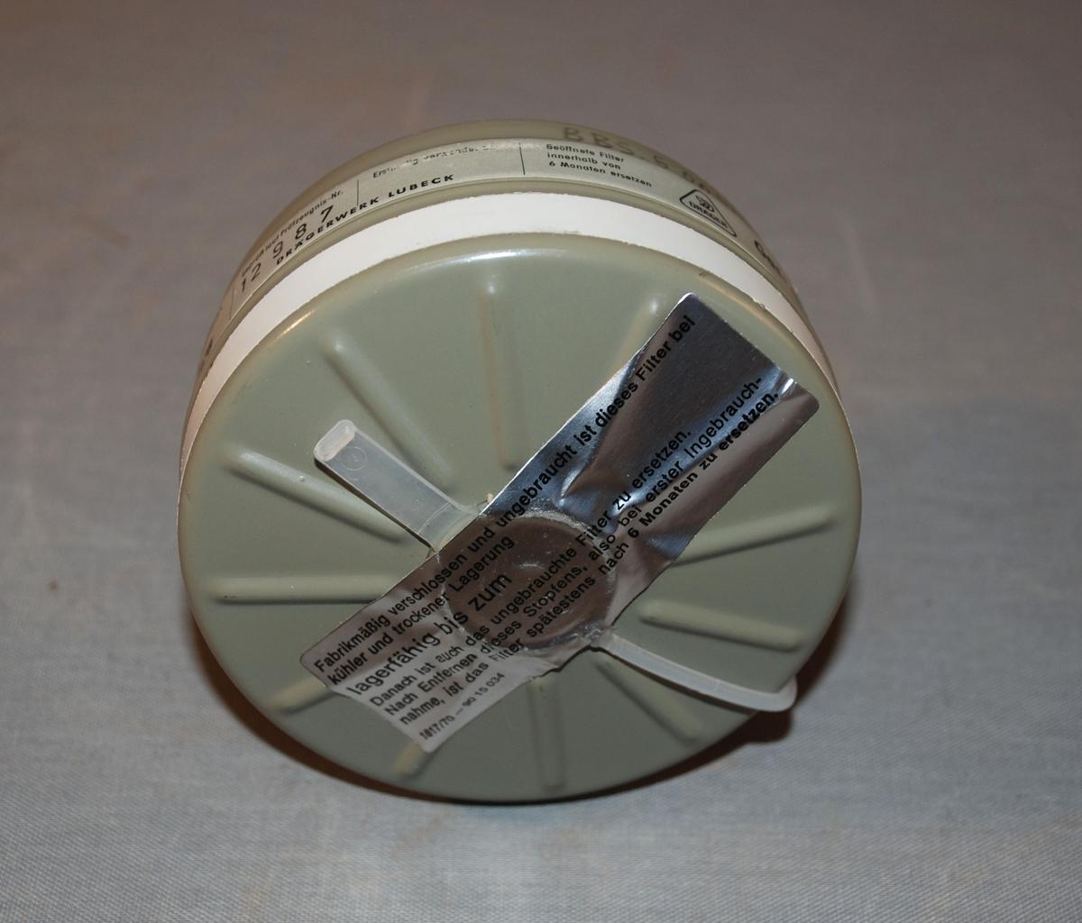 Gassmmaske med gass- og støvfilter, bruksanvisning og beholder med lokk til oppbevaring. Filterpatronen er et gass- og svevestøvfilter, sirkelrundt med plastkork over åpningen som skal festes til masken. Formen er sylindrisk med avrunding mot tilkoplingspunkt.