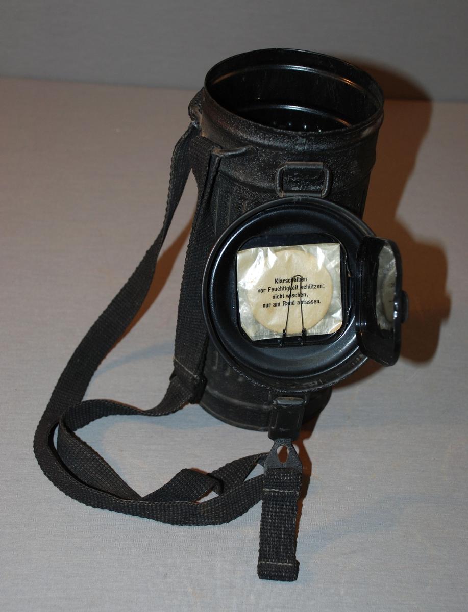Gassmaske med gass- og støvfilter, bruksanvisning og beholder med lokk til oppbevaring. Sylindrisk beholder med hengslet lokk. Sylinderen har vertikal profilering. Bærehåndtak festet til metallbøyler på utsiden av beholderen.Lokket lukkes med en spenne med hull som tres inn på en utvendig knott. På innsiden av lokket er det et rom med lokk, som inneholder bruksanvisning. I en lomme av vokspapir ligger en rund plastlomme, ikke åpnet.