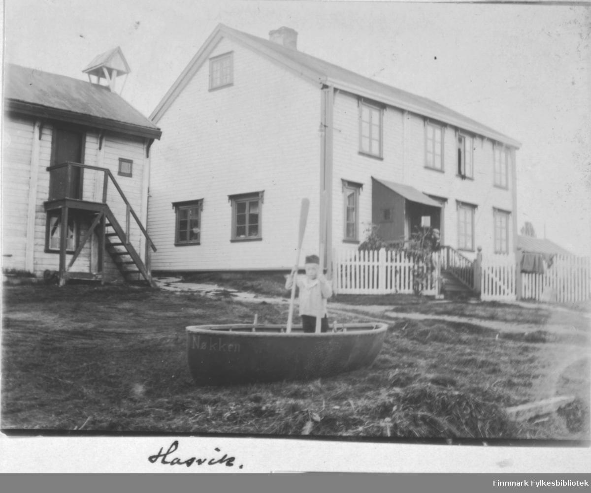 Hasvik, ca 1900? En liten gutt i lekebåt utenfor et hus. Arthur Wilhelm Buck fra Øksfjord overtok handelen i Hasvik i 1898