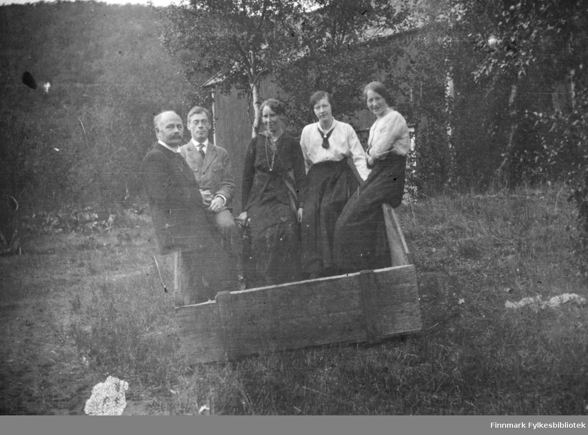 Fem personer, tre damer og to menn, fotografert mens de sitter på kanten av en trekasse i Rassejåkka i Tana. Alle sammen har på seg fine klær. I bakgrunnen ser man en bygning mellom trærne.