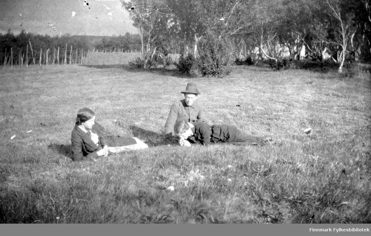 To damer og en mann ligger eller sitter på et jorde en fin augustdag. Mannen er Hans Gabrielsen. Mellom trærne i bakgrunnen kan man skimte et hus.