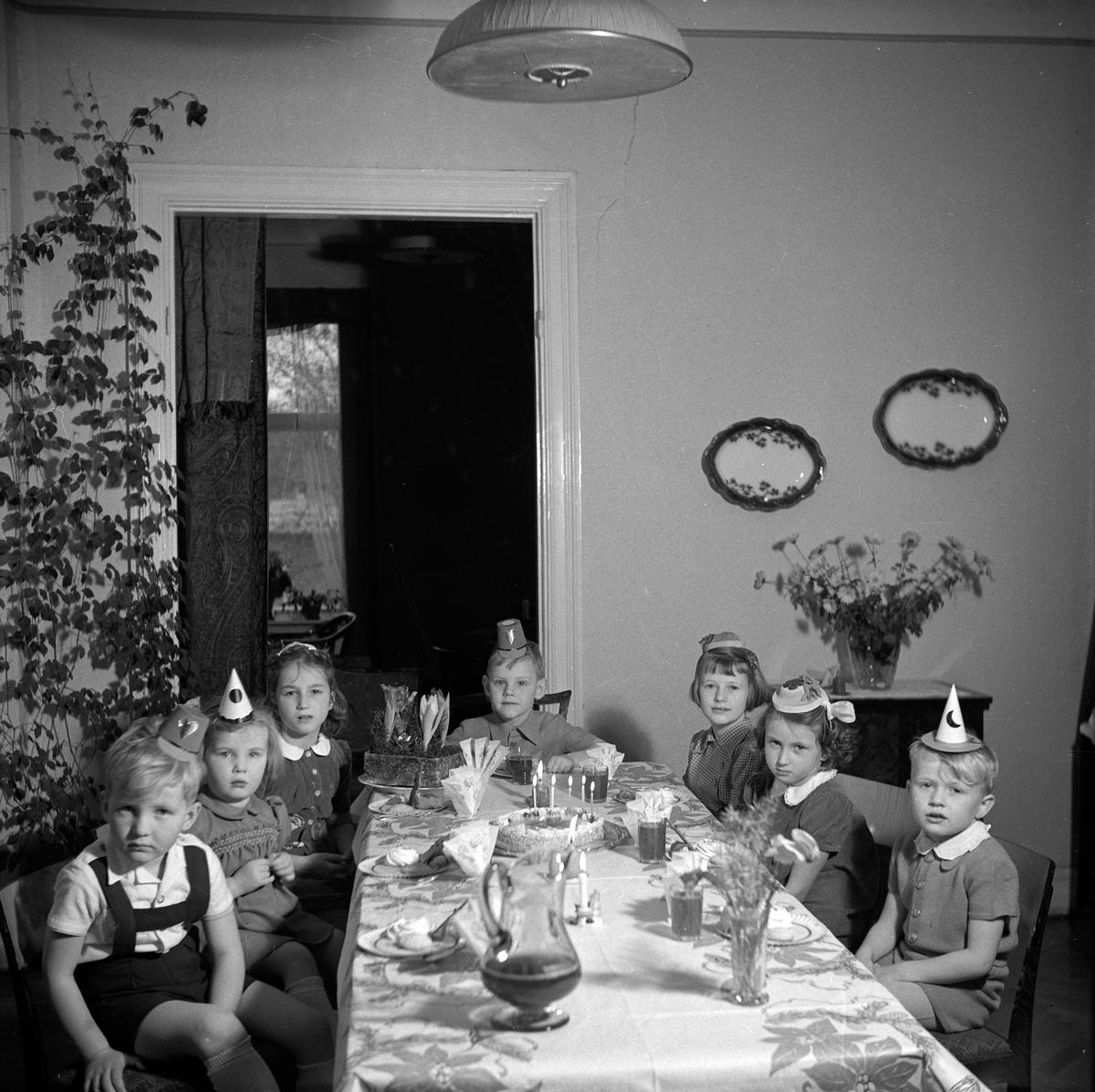 Barnen är på födelsedagskalas hos Olle Karlberg. Alla bodde på Kungsgatan 10. Huset ägdes av Jönköpings läns sparbank där även banken hade sina lokaler. Vid det dukade bordet längst fram från vänster sitter: Ulf Pettersson, Siv Pettersson, Karin Patzold, Olle Karlberg, Ingvor Lindahl, Monika Patzold och Jan Lindahl.