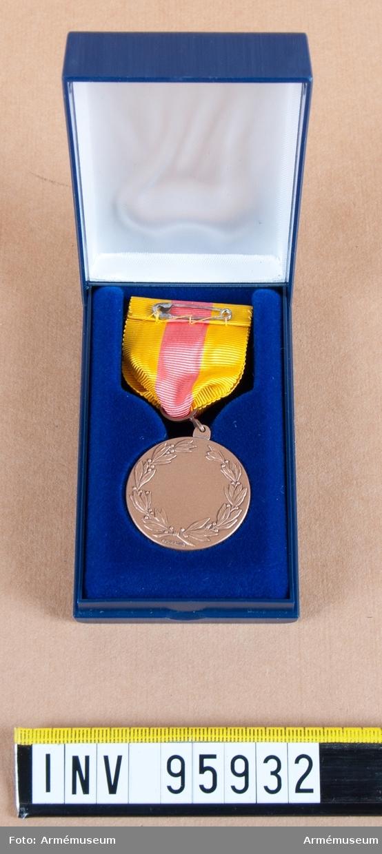 Kronobergs regementes (I 11) hedersmedalj i brons, 8:e storleken, 1971-1997.  Band: kluvet i gult, rött och gult.   Medalj i blå ask klädd med blå sammet och vit siden.
