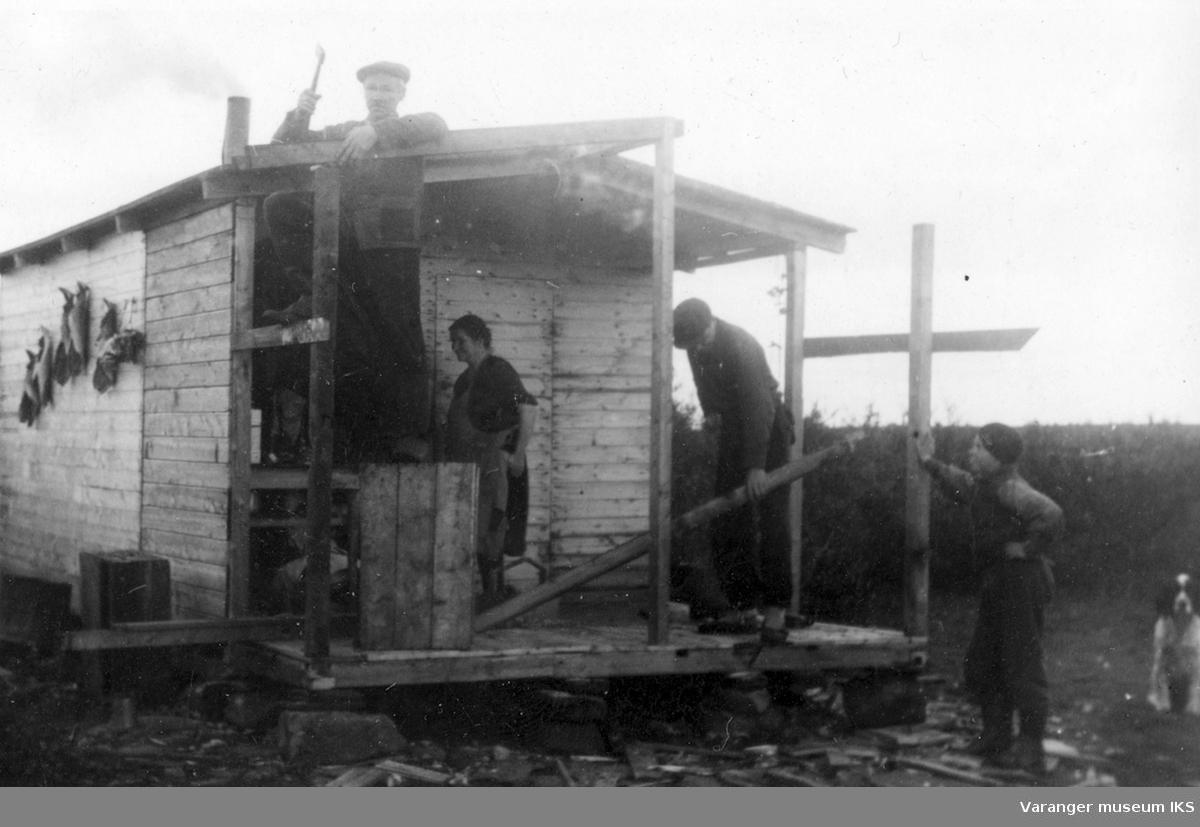 Bygging av hytta Fredheim på Viinikkaslåtta. Bildet er tatt i perioden 1939-1944. Avbildete er Nanna Riesto, Johan Riesto (på taket), hunden Jerv og to av Riestoguttene.