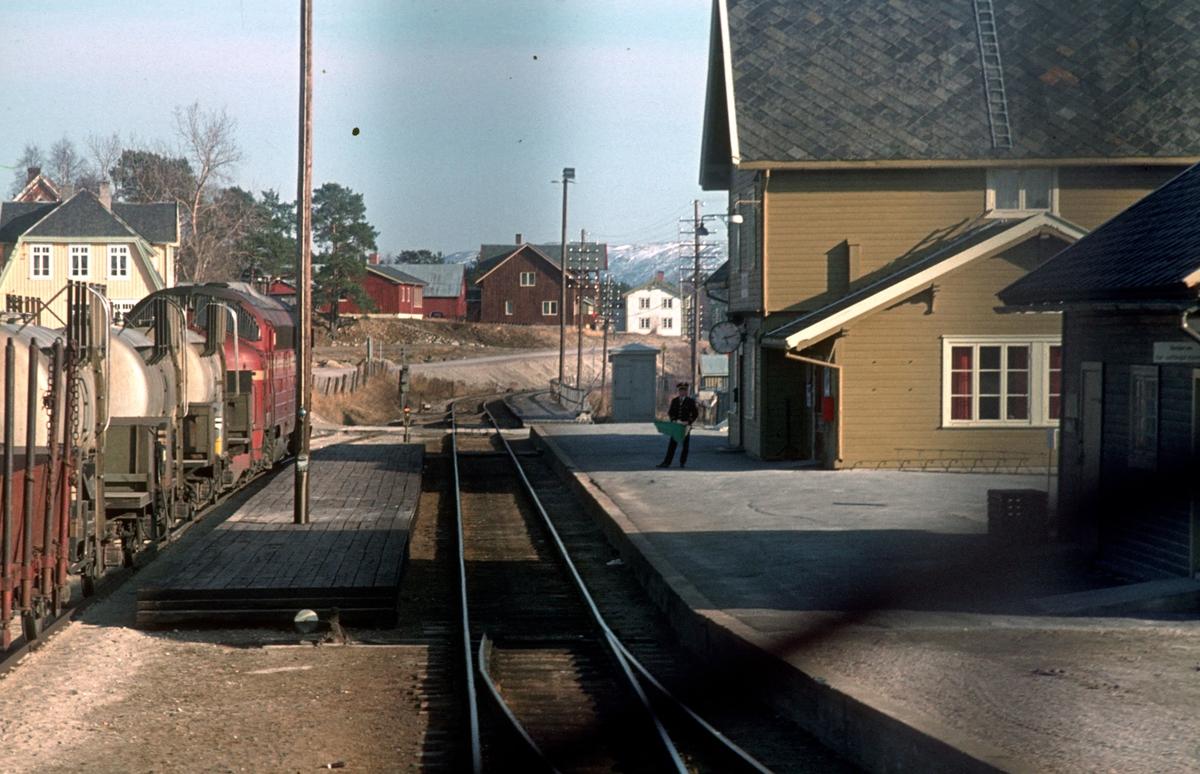 """Forbikjøring av godstog i Alvdal. Påskeslutt. Dagtoget 302 Trondheim - Oslo Ø var innstilt og ble kjørt i B-rute (senerelagt) fra Tynset. Et ekstra togsett gikk i tog 302 sin rute fra Tynset. Bildet er tatt fra lokomotivet i det ordinære, senerelagte toget. Signalstopp i Alvdal, og togekspeditøren viser signal """"Passer"""""""