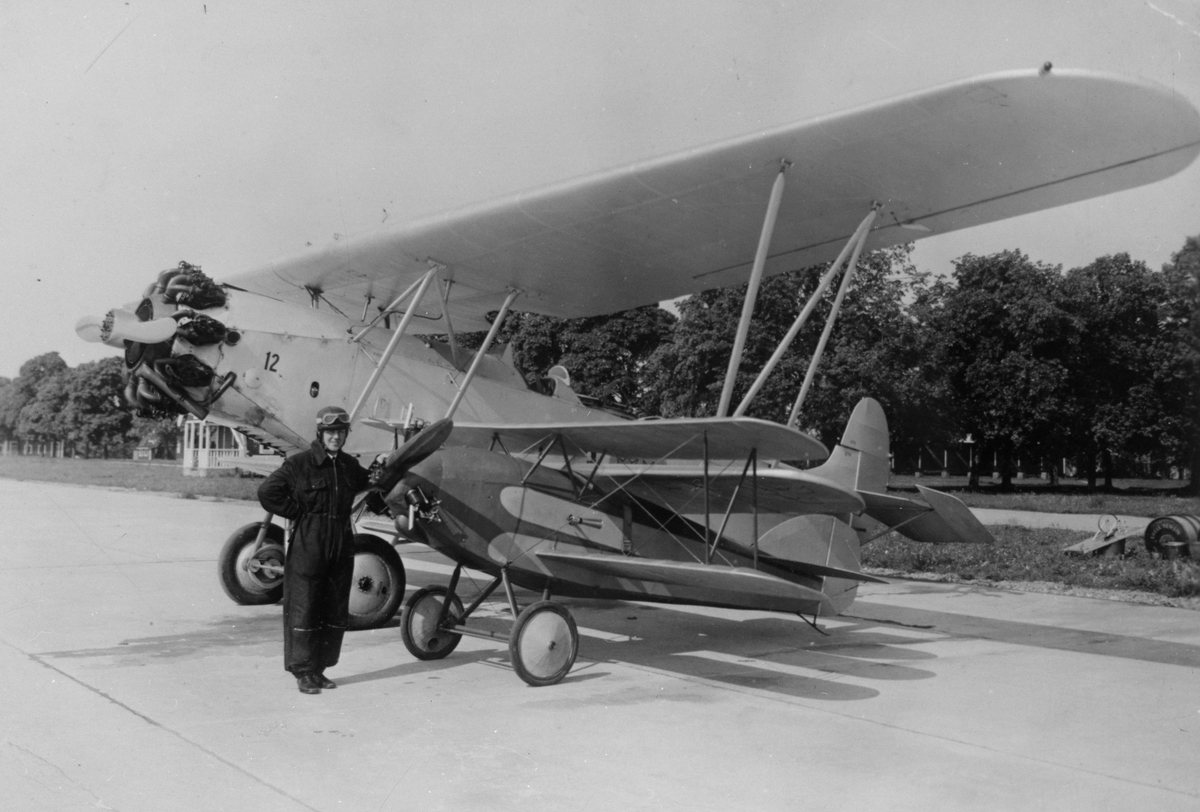 Porträtt. Tyghantverkare George Holmberg står i flygarutrustning framför sitt hemmabygge Holmberg Racer på Malmen. I bakgrunden står flygplan S 6.
