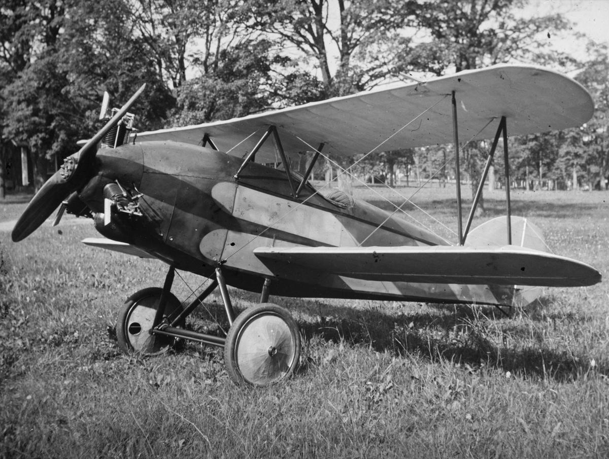 Civilflygplanet Holmberg Racer står på ett fält.