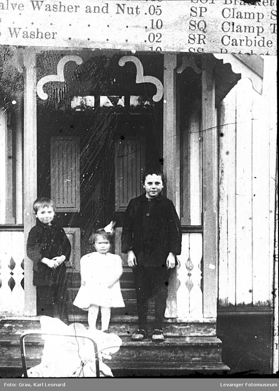 Gruppebilde, tre barn på trapp og et i barnevogn.