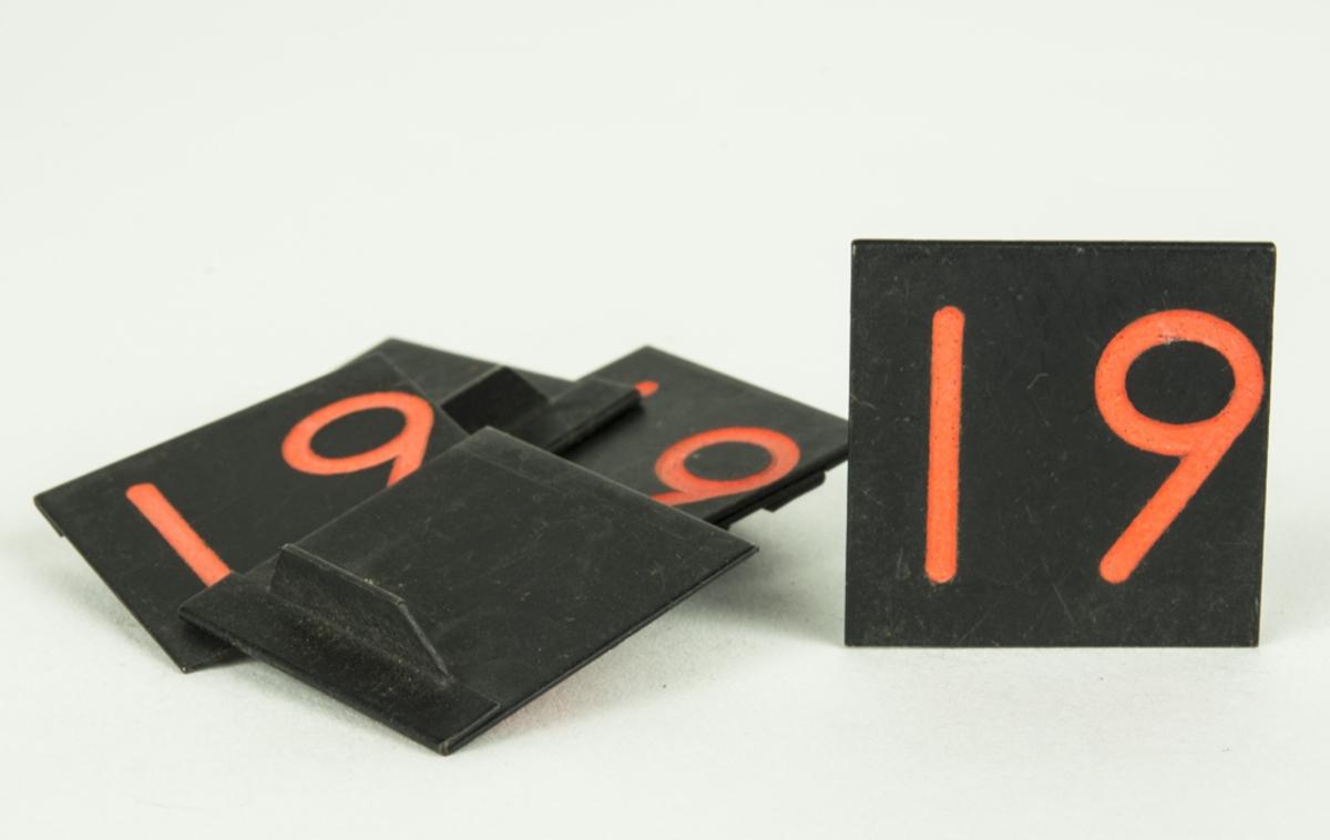Markerbricka med siffran 19. Sammanhör med ett större parti brickor, pilar och tecken.