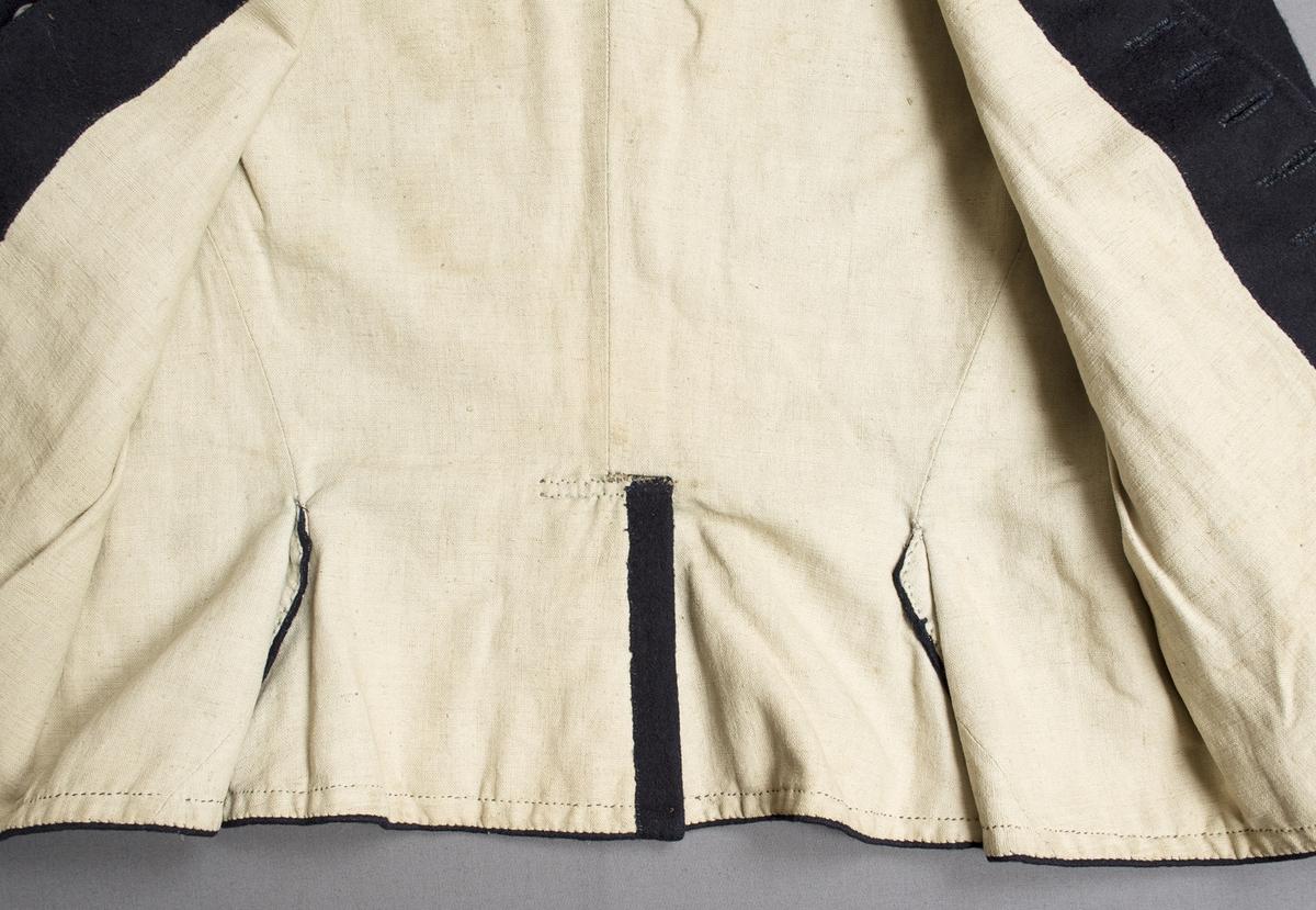 """Mörkblå manströja i vadmal. Tröjan har ståkrage, är helknäppt fram och har sprund och skörtflikar bak. Framtill knäpps tröjan med tolv silverknappar. Knapparna är stämplade """"ASB""""; en mästarstämpel som står för A Silfverberg, verksam i Ystad 1801-1841 (änkan drev verkstaden till 1849). De halvrunda knapparna är 21 mm i diameter och har graverat mönster på ovansidan.  Ärmens manschett, i samma tyg, är 75 mm bred med ett lika långt sprund som knäpps med två knappar. En kulformig knapp i mässing på var ärm; två knappar saknas. Axelbredd: 165 mm. Ärmlängd: ca 590 mm. Ärmen är sydd av två stycken. Tröjan är helfodrad med halvblekt, tuskaftat linne. Knapphålen är tränsade med blått lingarn. Märkt på insidan vid ena axeln med en hänglapp med texten: """"Inköpt  N° 11 a"""" (Först står det """"N° 4"""" men fyran har strukits över)."""