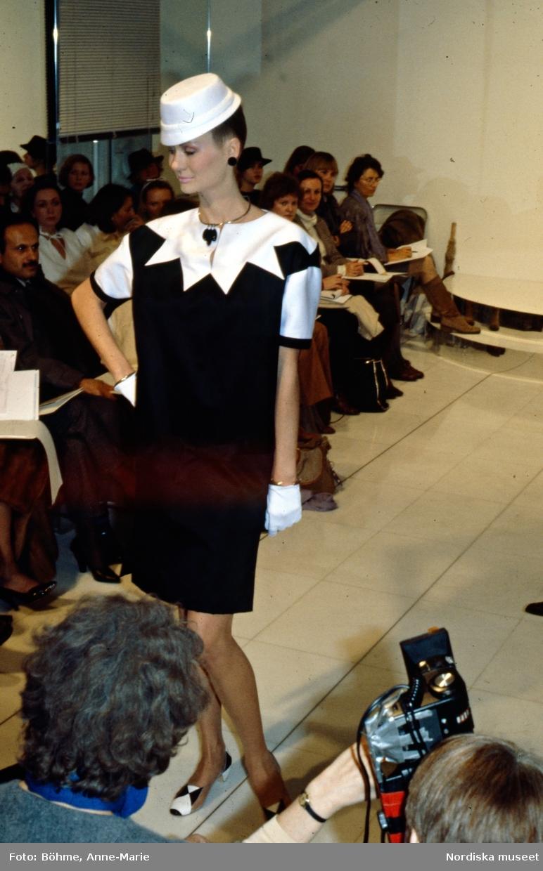 Modevisning. Modell i svart klänning med vit stjärnformad krage, vit hatt och smycken. Från Courrèges.