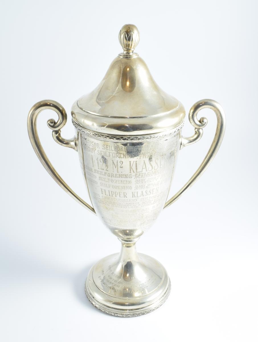 """Pokalen er en vandrepokal som ble vunnet under Sørlandspokalseilasen som ble arrangert årlig på omgang mellom Christiansands Seilforening, Lillesand seilforening, Grimstad Seilforening, Arndal Seilforening og Risør Seilforening. I tillegg til de fem sørlandsforeningene deltok også kongelig Norsk Seilforening fra Oslo. Pokalen var premie i 12,5 kvm -klassen og senere Flipper-klassen. Pokalen """"vandret"""" fra 1950 til og med 1981. I løpet av disse årene ble den vunnet av:  1950 Risør Seilforening """"Petrellen"""" Mads V. Norman """"Ulrikke"""" Aksel Prebensen  1951 Risør Seilforening """"Petrellen"""" Mads V. Norman """"Ulrikke II"""" Aksel Prebensen  1952 K.N.S Jr. Avdeling """"Hegra"""" Rolf Eilhardt Pedersen """"Småkryss II"""" Jens Erik Bøe  1953 K.N.S. Jr. Avdeling """"Småkryss II"""" Jens Erik Bøe """"Mauri II"""" Fritjof Foss  1955 Kr.Sand Seilforening """"Dixie II"""" Bjarne Birkeland """"Diddi III"""" Joh. P. Johnsen Jr.  1956 Risør Seilforening """"Petrellen"""" Mads V. Norman """"Blue Prince"""" Johan Arndt  1957 Risør Seilforening """"Satu"""" Nils Salvesen """"Maurie II"""" Per Gjermundsen  1958 Risør Seilforening """"Amigo"""" Peder Pedersen """"Mauri II"""" Per Gjermundsen  1959 Risør Seilforening """"Mauri II"""" Per Gjermundsen """"Tulla"""" Georg Gregersen  1960 Askerøy Seilforening """"Mac Mac"""" Audun Marcussen """"Tita"""" Jens Marcussen  1961 Risør Seilforening """"Petrellen"""" Mads V. Norman """"Ulrikke"""" Axel Prebensen  1962 Chr.ssand Seilforening """"Baby Doll II"""" Erik Dollis """"Kjartan V"""" Ole Jochumsen  1963 Chr.ssand Seilforening """"Baby Doll II"""" Erik Dollis """"Ninja"""" Tim K. Svensen  1973 Christianssand Seilforening Tom Jebsen / Ingrid Wiirsching Peter N. Prebensen / Stein Argsund Espen Høyby / Leif Hubert D.Y.  1974 Grimstad S.F. Asbjørn Næss / knut Frode Pedersen Pål Næss / Rolf Erik Nielsen Bjørn Bergshaven / Henrik Eriksen  1975 Grimstad Seilforening Vidar Pedersen / Jan Erik Hansen Knut Malde / Ruth Øvensen Bjørn Bergshaven / Reidun Gjertsen  1976 Kristianssand Seilforening Per Chr. Justnæs / Torgeir Skaiaa Richard Olsen / Kristin Olsen Hans Erik Jakobsen / Erik Amble  197"""