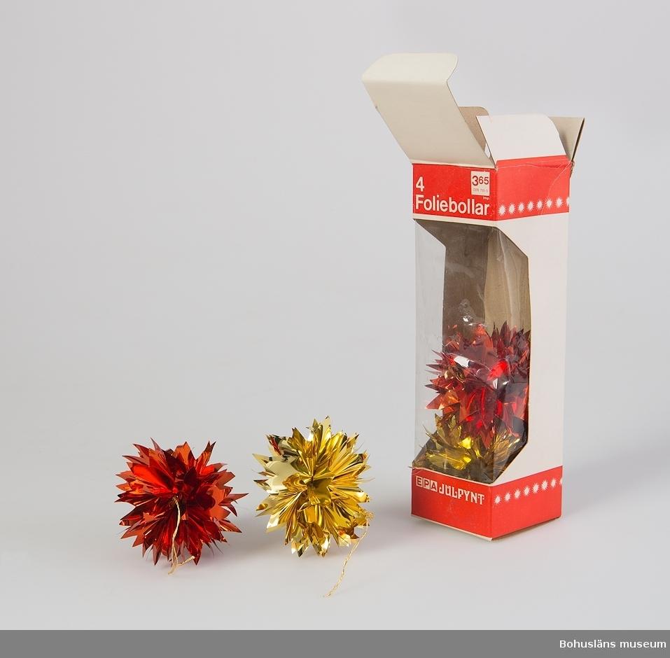 Julgransdekorationer av röd och guldfärgad metallfolie formade som taggiga bollar med hänge av snöre. Förvarade i originakarton med text: 4 Foliebollar EPA JULPYNT 3.65 [pris]