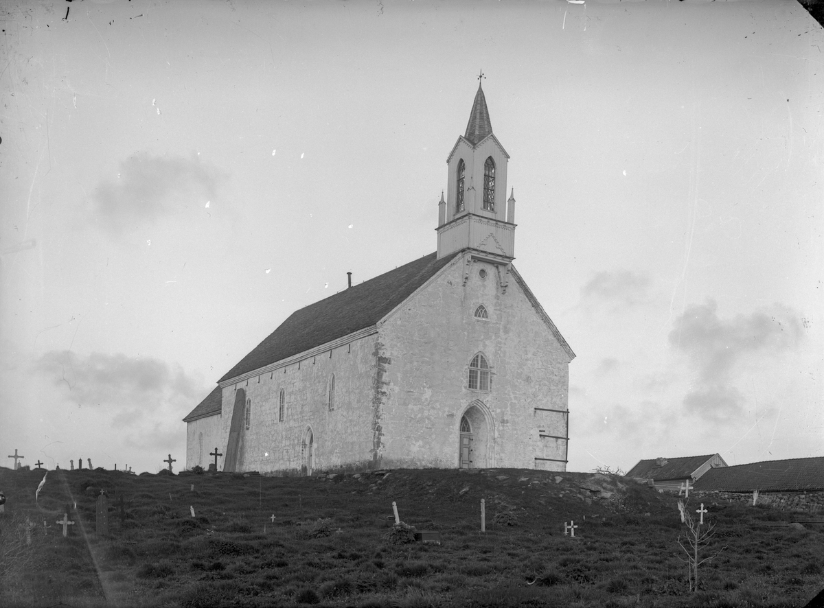 """Avaldsnes kirke. Mindre trekors på gravene i forgrunnen. Større jernkors på gravene i bakgrunnen. Trebygning til høyre. Bautasteinen """"Maria Synål""""  står et litt øst for kirken og lener seg mot kirkemuren."""