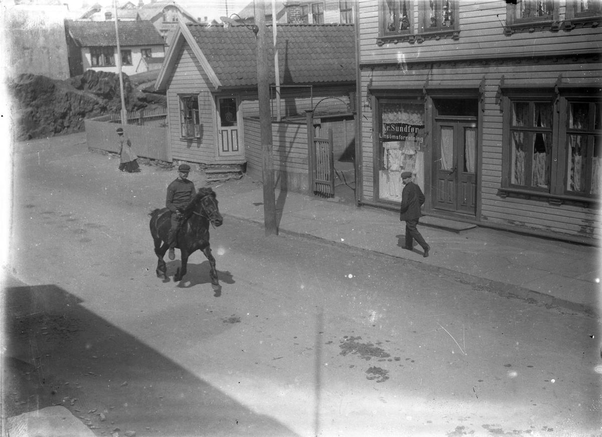Haraldsgaten ved Kolbeinshaugen. En mann ridende på en hest midt på gaten. En mann på fortauet på høyre siden. Trehus på høyre side og i bakgrunnen, i tillegg til et gjerde og en flaggstang og en annen person.