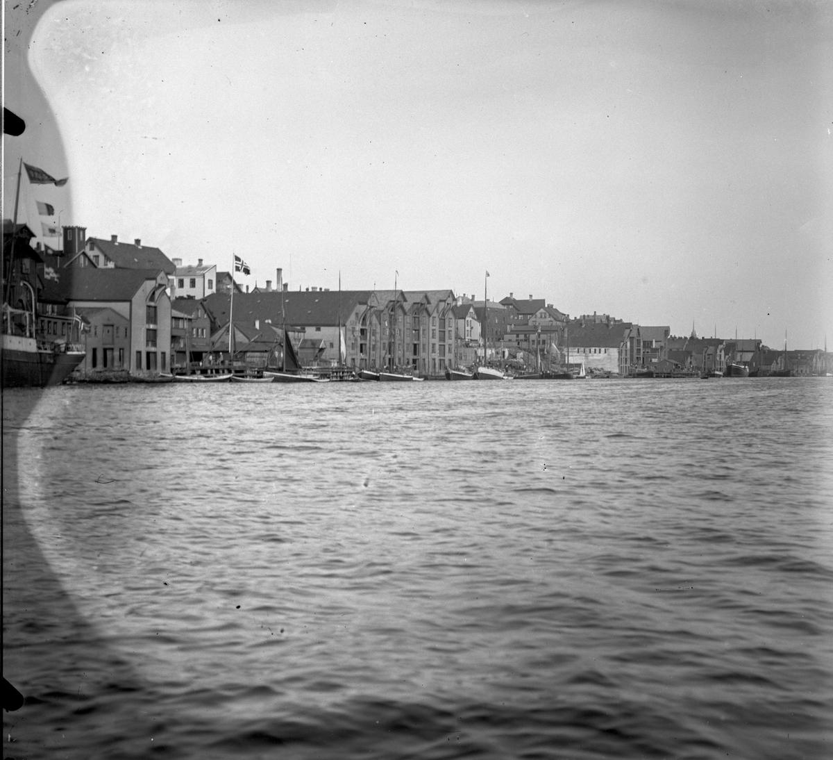 Kaien. Dampskip lengst til venstre.  Flere Fiskebåter, seilfartøy og et dampskip ankret opp ved kai i Smedasundet. Hus og andre bygninger i bakgrunnen. Flaggstang med norsk flagg.