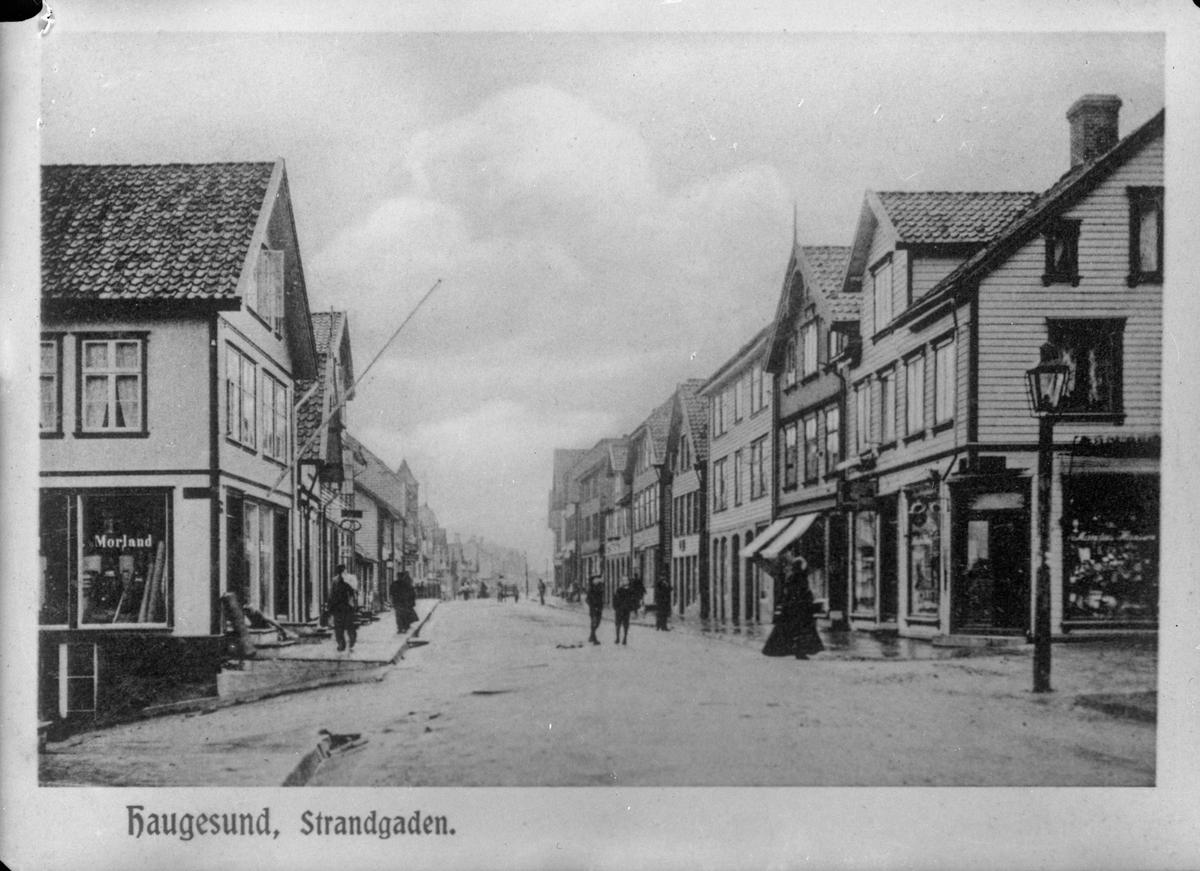 """Strandgaten i Haugesund sett fra syd i 1905. """"Morland"""" malt på vinduet på huset til venstre. Gaten midt på bildet. Gatelykt til høyre. Trehus på begge sider. Flere personer i gaten. Hest og kjerre i bakgrunnen."""
