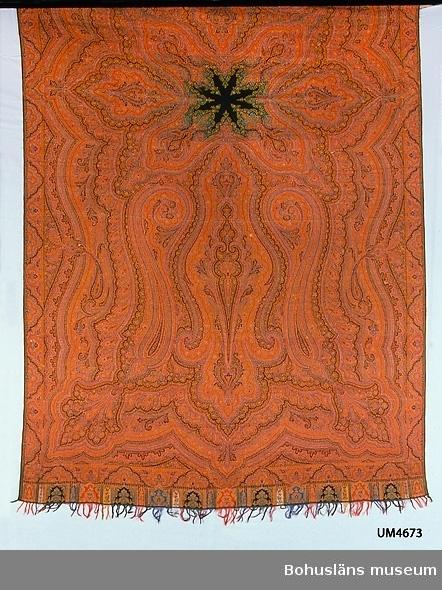Rektangulär helmönstrad schal för kvinna av Paisleytyp. Har ett detaljrikt orientaliskt mönster med böljande slingor. Färgerna i mönstret är rött, svart, vitt, gult och ljusblått. Ytterst i varje kortsida finns en bård med rutor som har olika bottenfärg. Mitt på schalen finns ett enfärgat svart stjärnmotiv. Förebilden kommer från handvävda schalar i Kashmir i nordvästra Indien (kashmirschal). Schalar med så här komplicerat mönster är gjorda i jacquardvävstol. Garnet troligen syntetfärgat. Därav dateringen till tidigast 1860-tal. Schalar av Paisleytyp miste sin populäritet på 1870-talet. Sista schalen av den här typen i Paisley vävdes 1886. Paisleyschal användes som benämning på schalar av den här typen, även sådana som inte är vävda i Paisley (i Skottland). Var denna är vävd är inte känt. Mönstret är likt UM022926 men denna schal är av sämre kvalitet. Den har grövre inslagsgarn och är mera löst slagen, de avklippta trådändarna på baksidan är längre, mönstret mindre distinkt. Flera små hål på ena halvan av schalen. En lagning.  Ur handskrivna katalogen 1957-1958: Äkta schal Mått c:a 3,06 x 1,52 cm. Det ornamentala mönstret i rött, gult, blått o svart. Frans. Malhål.