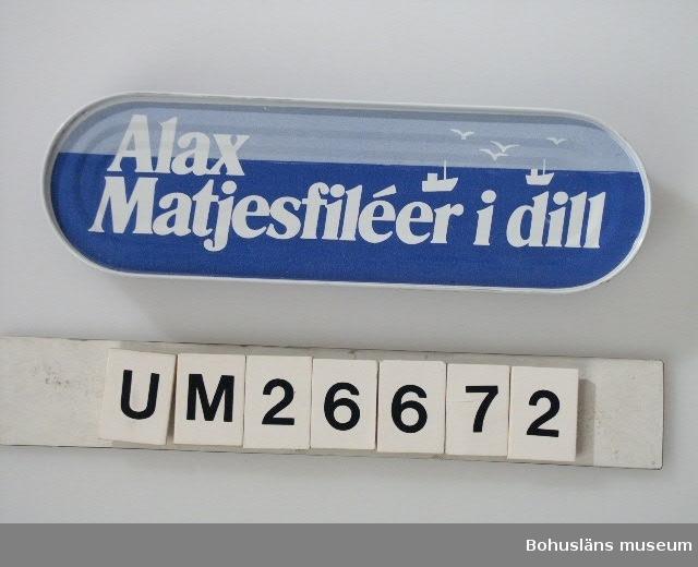 """394 Landskap BOHUSLÄN  Avlång burk med avrundade ändar. Tryck dekor i mörkblått, ljusblått och vitt Tryckt dekor: """"Alax Matjesfiléer i dill"""". På botten innehållsförteckning. Från Albert Axelsson & Son, Klädesholmen  Om givaren: Se UM26667"""