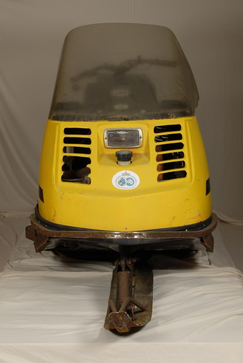 Motorisert gjenstand med 2 drivbelter, én styreski og gult karosseri. Det er en todelt avlang salpute med ryggstøtte i midten.