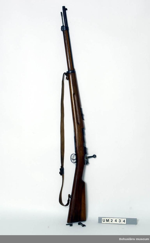 """Kulgevär C-G 6,5 x 55.  Ur handskrivna katalogen 1957-1958: Armégevär, mauser L. 126 cm, i gott skick; 1900; på manteln """"O.G 54600"""". Remmen b) av läder. Läskstång c) L. 69,8 cm."""