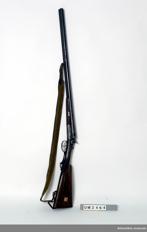 Kaliber 12 Ur handskrivna katalogen 1957-1958: Tvåpipigt jaktgevär 120 cm längd Tillverkare Husqvarna vapenfabrik. Träkolv m. vissa delar av horn. Axelband i läder o tyg. Damascerat i pipan.  Lappkatalog: 55  För uppgifter om givaren, se UM2249.