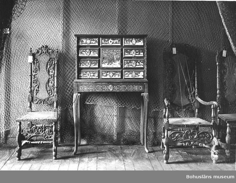 Föremålet visas i basutställningen Uddevalla genom tiderna, Bohusläns museum, Uddevalla.  Stol av engelsk-holländsk typ, troligen i valnöt med flätad sits och ryggbricka i rotting. Från 1660-talet till början av 1700-talet, det vill säga att de är tillverkade under den karolinska tiden.  Givaren, Gustaf Hegardt, var sekreterare i Uddevalla Musei Styrelse.  (Stolen till vänster om kabinettskåpet på foto från tidigt utställningsarrangemang på Uddevalla museum UMFA53086:0976.)  Ur handskrivna katalogen 1957-1958: Stol i barock H. 133; sitsens mått: 38,5 x 46,5 cm; som föreg, men ej krönt. Maskhål, f.ö. hel.  Lappkatalog: 82  I den äldsta tryckta katalogen över Uddevalla museum samlingar - Uddevalla Musei Historiska Samlingar 1869, avd. F Saker från yngre Medeltiden räknad till 1550, upprättad av artisten och fornforskaren samt intendenten över Göteborgs historiska museiavdelning Gustaf Henrik Brusewitz: Nr 35: En äldres stol, hitskänkt av kammarherrinnan af Christiernin, född Hegardt. Hr Hegardt har härom berättat att framlidne kammarherren M. af Christiernin ägt ett halft dussin dylika.  Enligt UM000601: Michael af Christiernin 1785 - 1862.  I födelseboken Uddevalla församling C:5 står antecknat 1785 17 mars Majoren och rådmannen Harald Christiernin - - - Christine Koch, 21 år - - son Michael födt .   I födelseboken Uddevalla församling C:7 står antecknat 1813 Harald Josias, Föräldrar: Herr Michael af Christiernin och fru Jeanetta Hegardt, 26 år.  Harald af Cristiernin. Överste, konteramiral. Född 1751 Hille, Västmanland. Död 1799 1/5 i Karlskrona.   Gift 1784 1/6 i Uddevalla. Adlades 1751. Gift med Christina Koch. Född 1764 16/8. Död 1829 7/3 i Kristinedal, Uddevalla.   Barn: Mikael af Christiernin. Kammarherre. Född 1785 16/3 i Uddevalla. Död 1862 31/1 i Uddevalla. Gift med Johanna Cornelia Hegardt (1787-1875).  Den så kallade Christierninska kyrkogården, strax intill Bodelebäcken nära Gustafsberg söder om Uddevalla, är en privat begravningsplats tillkommen 1832 då 