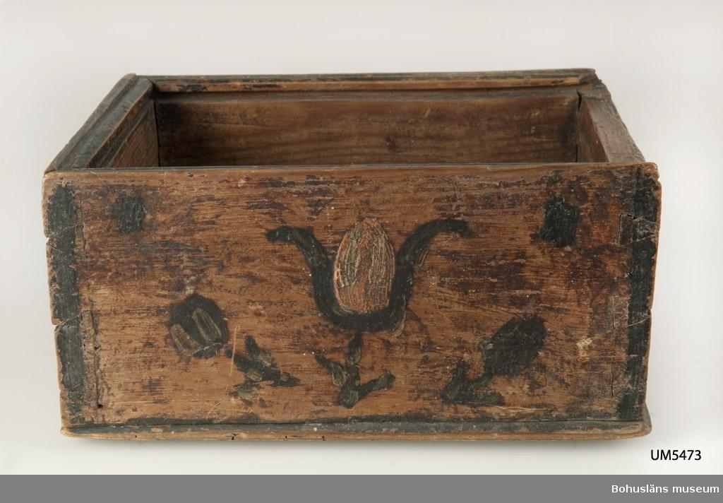 """Ur handskrivna katalogen 1957-1958: Trälåda """"B.O.D. 1791"""" Mått: 23 x 18 x 11 cm; sinkade hörn, har haft skjutlock; brun m. målad dekor och inskr. i grönt, rött och vitt. Maskhål.  Lappkatalog: 84"""
