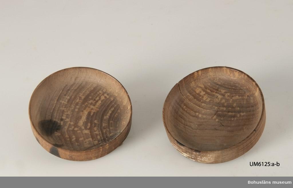 UM6125:a-b Ur handskrivna katalogen 1957-1958: Två små träfat diamet. 5,6 cm. H.: 1,1 cm. Det ena föremålet något sprucket.  Lappkatalog: 66