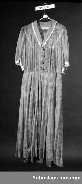 Klarblå tyllklänning med vita prickar. Klänningen har avskuren midja. Knäppning framtill med knappar klädda i tyg. Kort ärm. Vit spets runt krage och ärmarnas nedre kant.