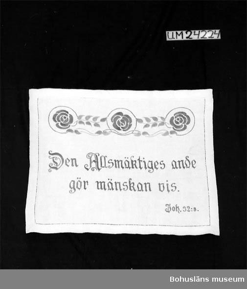 """Broderier i blått och grönt merciserat bomullsgarn. Tre blå rosor och gröna blad. Text: """"Den Allsmäktiges ande gör mänskan vis"""". """"Joh. 32:8"""".  Henning Wikström dog 21 december 1990, 97 år."""