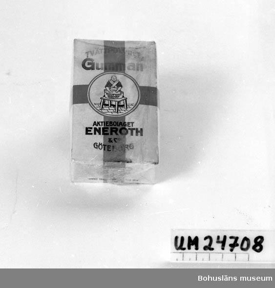 """471 Tillverkningstid 1940-TAL ? 410 Mått/Vikt  TJ, 3.5 CM  Fyrkantig förpackning. Omslagen med plastmaterial. Vit bakgrund med blå text. Rött kors runt om hela förpackningen. Text framsidan: """"TVÄTTPULVRET Gumman AKTIEBOLAGET ENEROTH & CO GÖTEBORG"""". På baksidan är de en bruksanvisning och på kortsidorna står det: """"Gummans Tvättpulver är utmärkt för tvätt av linne, bomull, ylle, siden och konstsilke, färgat och ofärgat. Det är lätt lösligt i kallt vatten. Även vid skurning och annan rengörning kan det med fördel användas. Oöppnad förpackning."""