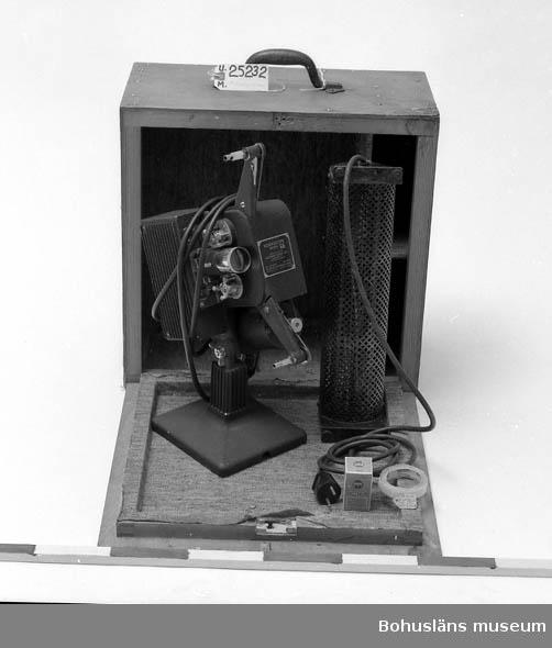 """471 Tillverkningstid 1930 CA 410 Mått/Vikt !LÅDAN:L:47.5 B:25 H:47.5 594 Landskap BOHUSLÄN Brun trälåda med bärhandtag. Svart projektor. Metallplåt med text:  """"KODASCOPE MODEL EE MADE IN U.S.A. BY. EASTMAN KODAK CO ROCHESTER N.Y.  TRADE MARK REG. U.S. PAT. OFF. 100-125 VOLTS 850 WATTS FOR USE WITH  SLOW-BURNING FILM OLNLY PATENTS IN U.S.A. 1,461,794 1,507,357"""". I lådan finns en svart likriktare, filmcement samt ett lås. A. Andersson filmade för Uddevalla stad under 1930-40-50-talen och  filmerna visades på denna kamera. Bohusläns museum har filmer i sitt arkiv som han gjort."""