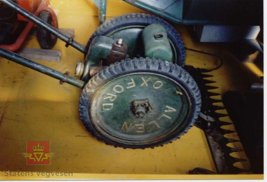 Grønn og svart motorslåmaskin på to hjul. Lagd i hovedsak av metall, med dekk av gummi. Motoren er besindrevet, 1-sylindret type av fabrikat Villers. Motoren startes ved hjelp av snor. Merking fra produsent på motor og maskin.