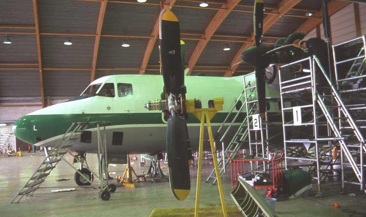 Lufthavn/flyplass. Bodø. Widerøes anlegg Langstranda. En person. Ett fly, LN-WFL, DHC-7-102/ Dash7 under vedlikeholdsarbeid.